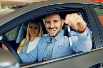 Couple holding up new keys to a new car