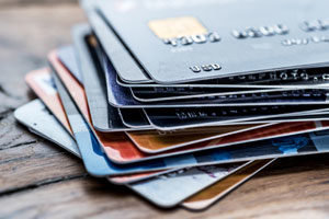 Stack of colorful credit and debit cards on a wooden table.