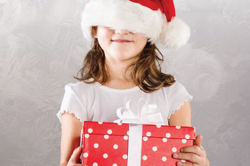 young girl in red santa hat covering her eyes smiling and holding red wrapped gift box
