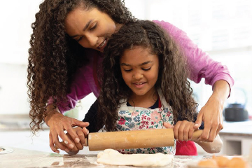 mother helping daughter together in kitchen baking and rolling out dough