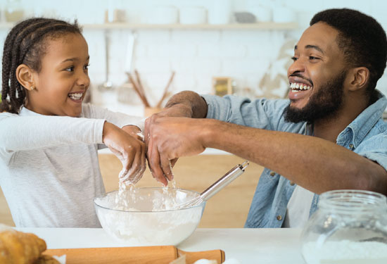 Father and daughter making cookies at the kitchen.