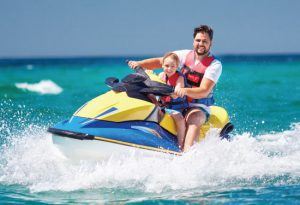 Father ans son having fun on a jet ski in the water smiling