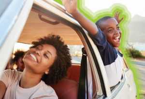 mother and son driving with windows down, both smiling