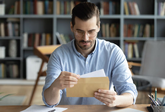 Man opens envelope with check inside.