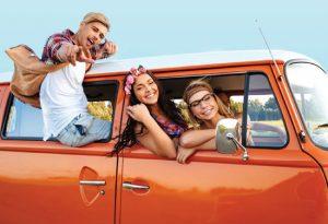Teenagers riding in an orange car.
