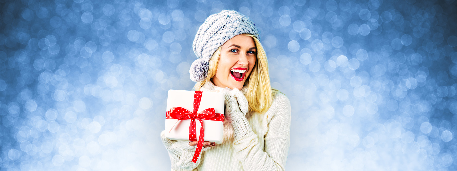Smiling female wearing sweater, mittens, and winter hat holding wrapped present with joy