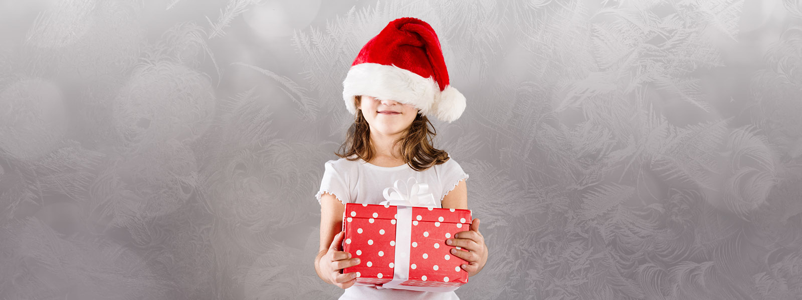 Girl holding a gift with a Santa hat covering her eyes.
