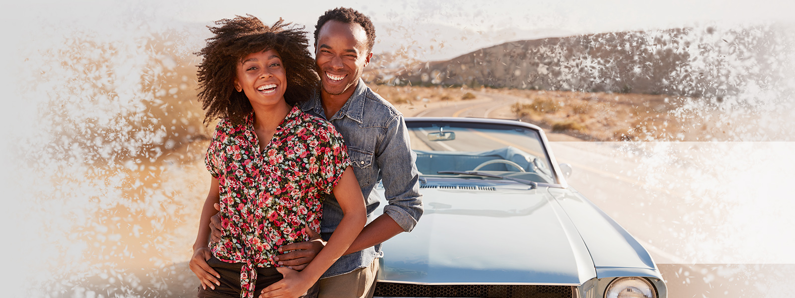 Couple smiling next to their new car