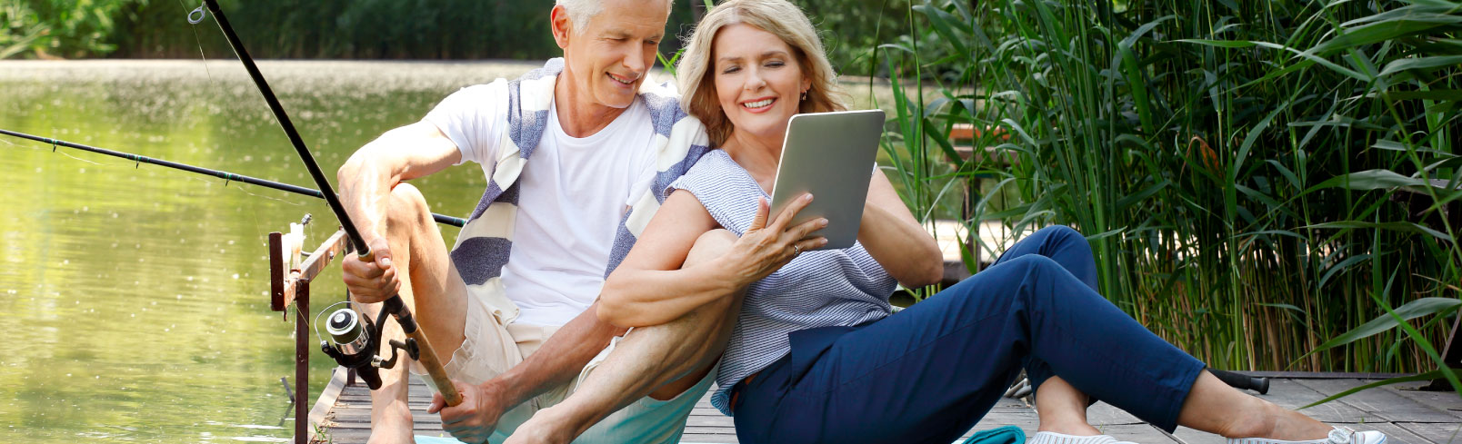 Older couple on an ipad doing onle banking while fishing