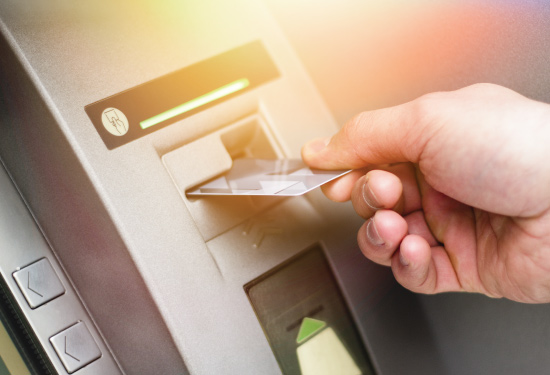 hand placing debit card into atm