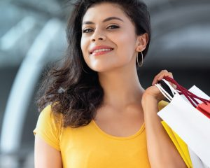 young female smiling while holding shopping bags