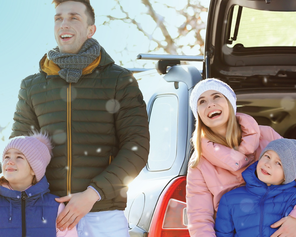 family in winter weather clothes gathered and smiling playing outdoors