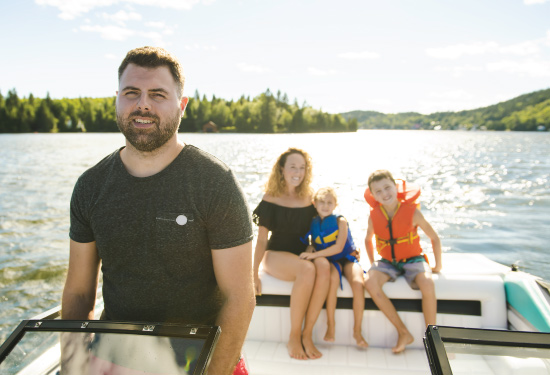 Family boating together on lake, with mother, father and two children wearing life-jackets