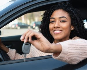 african american young adult holding keys to her newly purchased car