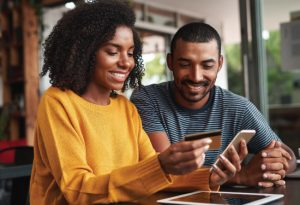 couple looking at smartphone and smiling, using debit card to make a purchase on phone