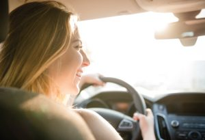 female driver smiling with sunshine in background