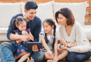 asian american family sitting together on floor looking at tablet together and smiling and laughing
