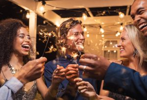 diverse group of friends holding sparklers and celebrating the new year