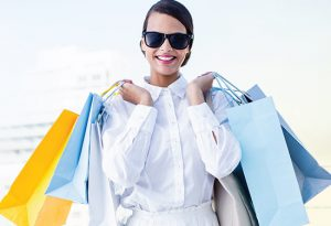 adult female wearing sunglasses and smiling holding shopping bags over her shoulders
