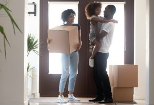 african american family moving into their newly purchased home, carrying in boxes in entryway and smiling