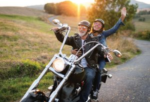 Adult couple enjoying their motorcycle on a winding road