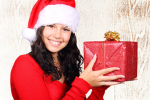 Young lady in red holing a gift and smiling