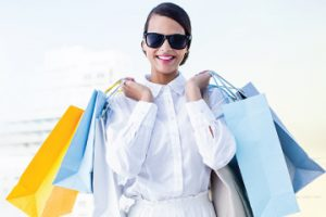 Woman wearing sunglasses and smiling holding shopping bags over both shoulders