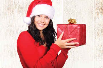 Woman in red sweater and red santa hat holding wrapped gift and smiling